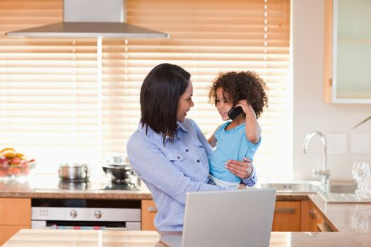 Mother and daughter using notebook and cellphone in the kitchen