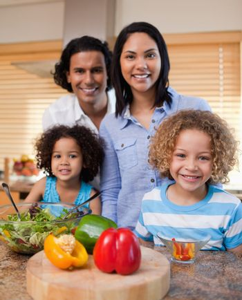 Family with salad together in the kitchen