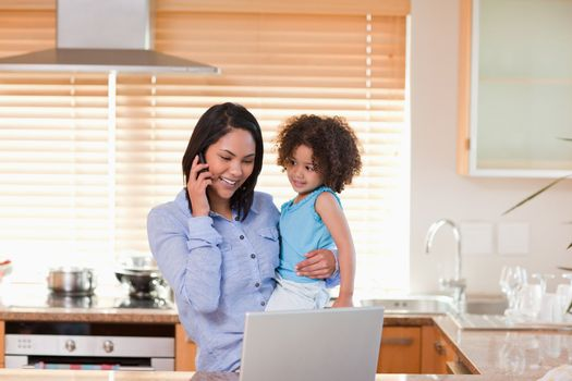 Mother and daughter using cellphone and laptop in the kitchen to
