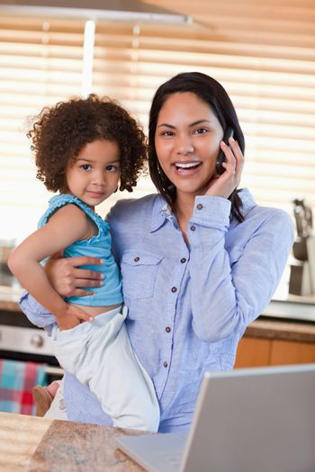 Mother and daughter using cellphone in the kitchen together