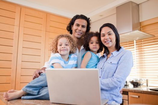 Happy family with laptop standing in the kitchen together