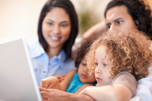 Cheerful family using laptop together