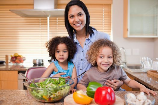 Mother and her daughters preparing salad in the kitchen together