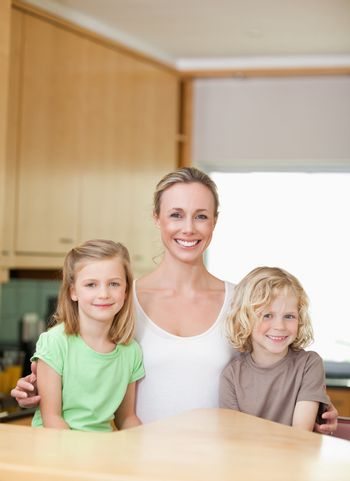 Mother with her daughter and son in the kitchen together