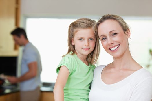 Mother and daughter together with father in the background
