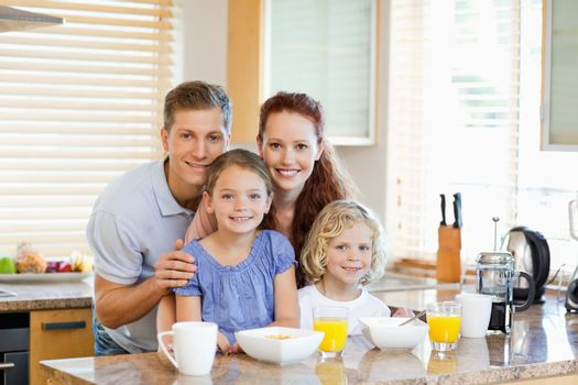 Family together with breakfast standing behind the kitchen count