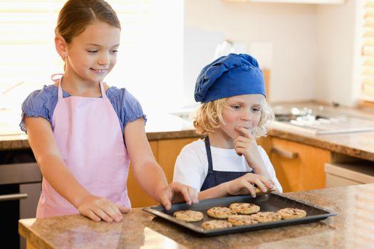 Siblings stealing cookies