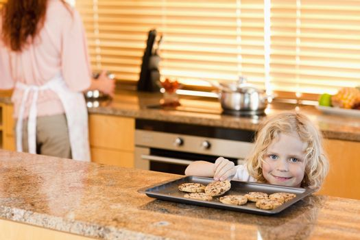 Boy stealing a cookie while his mother is not watching