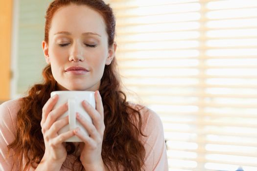 Woman enjoys the smell of her coffee