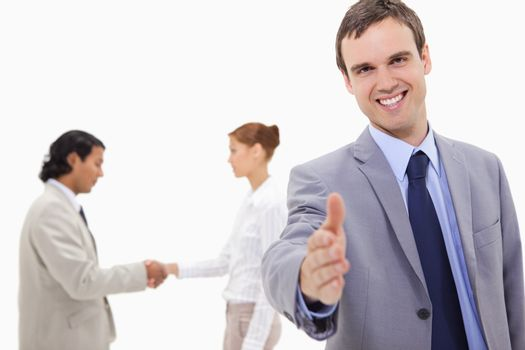 Businessman extending hand with hand shaking colleagues behind h