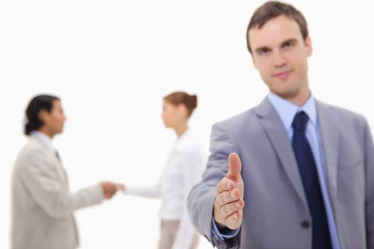 Businessman offering hand with hand shaking colleagues behind hi