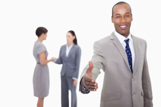 Smiling businessman offering his hand with hand shaking colleagu