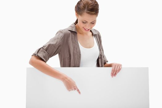 Woman pointing down at blank signboard
