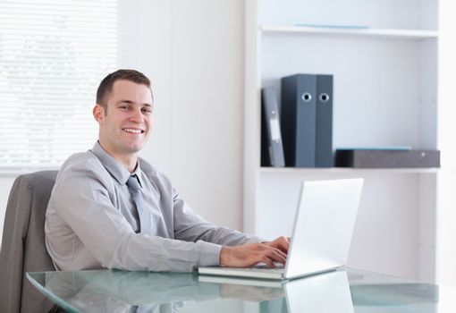 Satisfied businessman working on his laptop