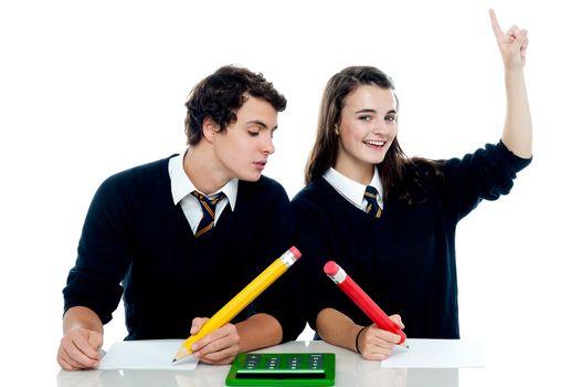 School boy peeping into the girls answer sheet