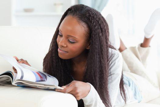 Woman looking at catalog on sofa