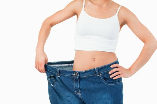 Thin woman wearing too large jeans