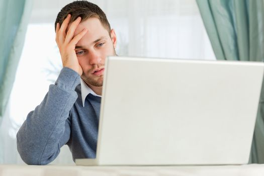 Businessman annoyed by his laptop in his homeoffice