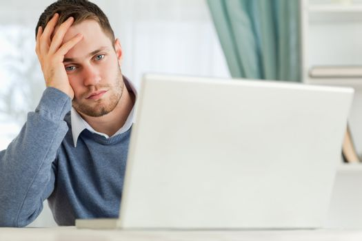 Businessman annoyed by notebook in his homeoffice