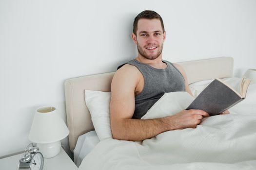 Smiling man reading a novel