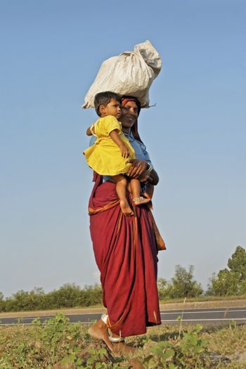 Female farm worker making her way home with babe in arms, baggage carried on her head, in bare feet in the hinterlands of maharashtra, India wearing ankle bracelets. September 29th, 2012, editorial
