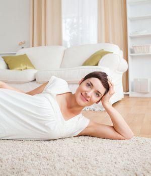 Quiet woman lying on a carpet