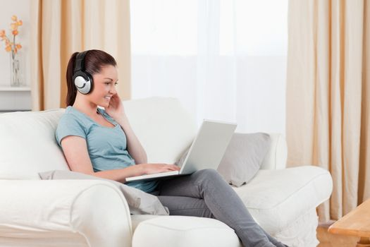 Gorgeous woman with headphones relaxing with her laptop while si