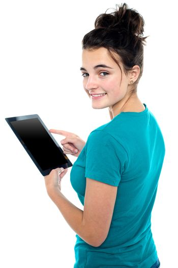 Trendy young casual girl operating tablet device