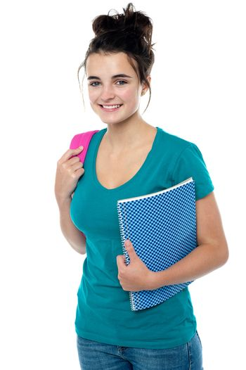 College student carrying backpack and spiral notebook