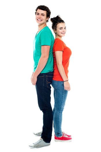 Adorable young couple posing back to back