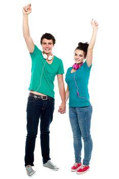 Strong bonding of cheerful teen couple enjoying music
