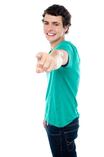 Young guy pointing you out with his stretched left arm