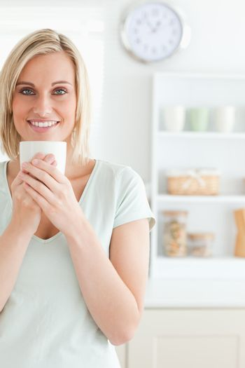 Portrait of a woman taking in smell of coffee looking into the c