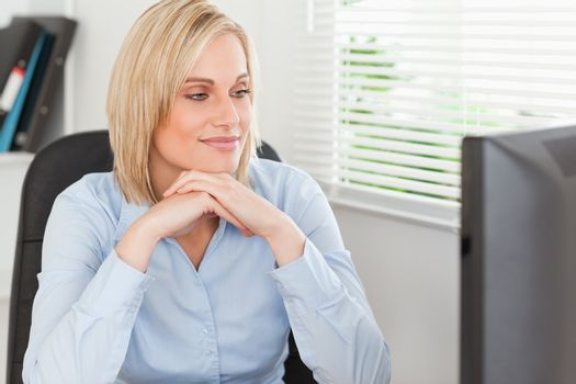Cute blonde woman with chin on her hands behind a desk looking a