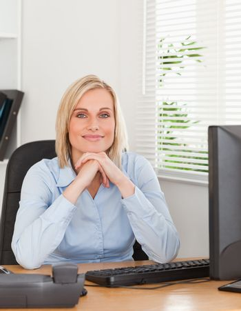 Smiling blonde woman with chin on her hands behind a desk