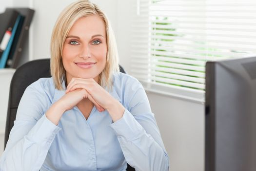 Cute blonde woman with chin on her hands behind a desk