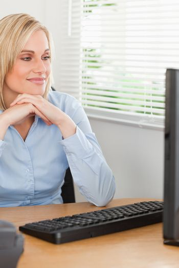 Charming blonde woman with chin on her hands behind a desk looki