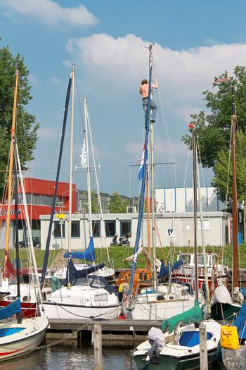 The man at the mast sailing yacht in the port of Huizen. Netherlands
