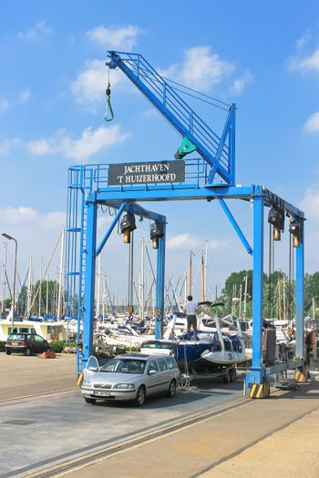 Crane unloading a boat with a trailer on the pier Huizen. Netherlands