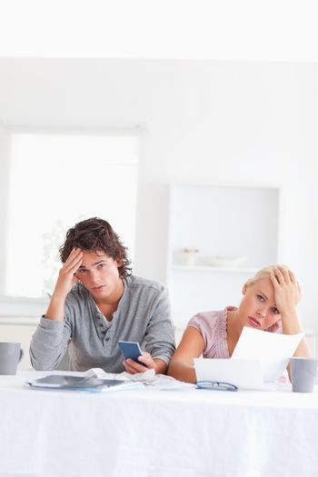 Worn out couple calculating their expenses