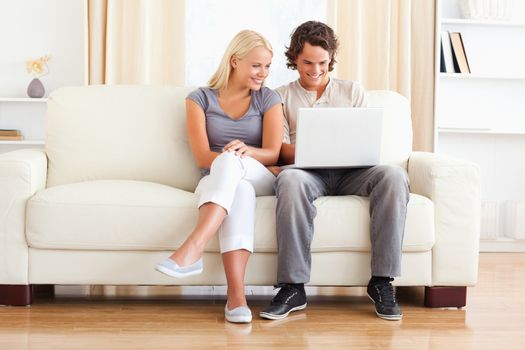 In love young couple using a laptop while sitting on a sofa