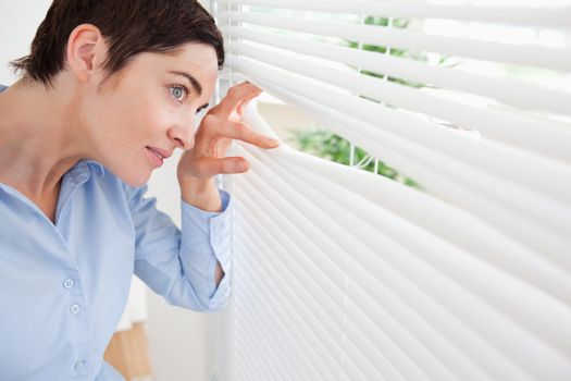 Good-looking brunette woman peeking out a window