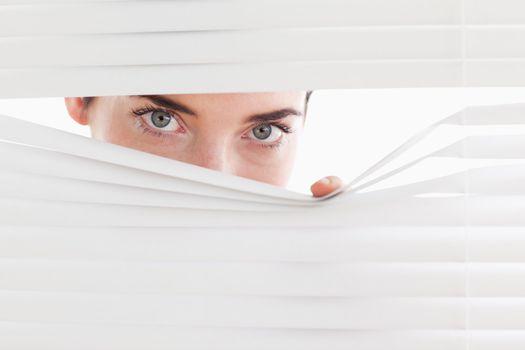 Brunette businesswoman peeking through a venetian blind