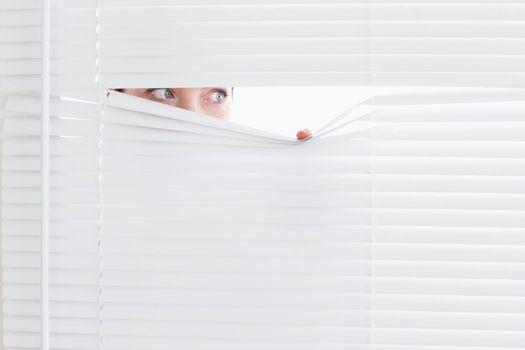 Businesswoman peeking out of a window