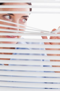 Beautiful businesswoman peeking through a venetian blind