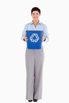Businesswoman showing a recycling bin