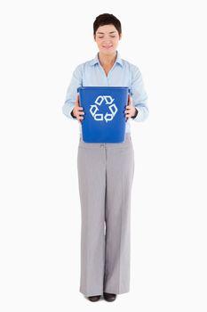 Businesswoman holding a recycling bin