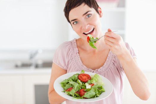 Good-looking woman eating salad