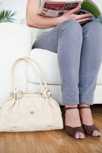 Part of a good-looking Woman on a sofa with a bag and a magazine
