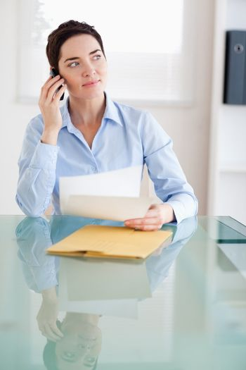 Businesswoman with papers on the phone